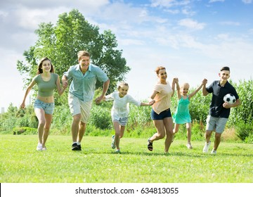 Large family happily playing and running together outdoors on green meadow in park