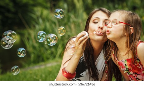 Family happiness and carefree concept. Mother and daughter little girl having fun blowing soap bubbles together in park, green blurred background