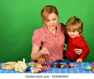 Family happiness and Easter celebration concept. Woman and little boy with cheerful smiles. Mother holds son on green background. Mom and child spend time together making Easter decorations.