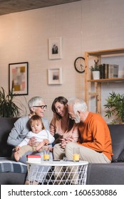 Family, happiness, generation, home and people concept - happy family sitting on sofa with one year old baby