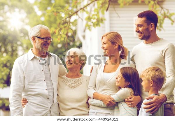 Familie, Glück, Generation, Haus und Menschen Konzept - glückliche Familie vor Haus im Freien