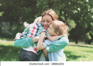 Family happiness! Happy mother tenderly embracing her two sons children on grass in spring day, warm feelings of the mother, lifestyle moment