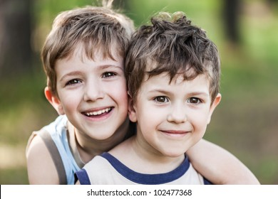 Family happiness - two little smiling child boy brothers walking outdoor