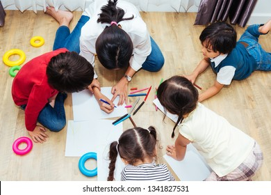 Family happy children group kid boy and girl kindergarten paint drawing on peper teacher education at interior playroom