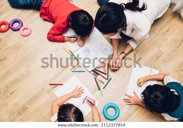 Family happy children group kid boy and girl kindergarten paint drawing on peper teacher education at interior playroom, back to school concept