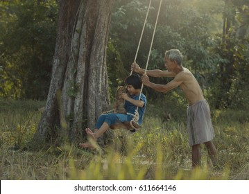 Family Happy Time : The little girl playing the swing with her father in the forest.