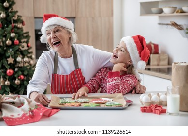 Family harmony. Portrait of happy grandmother and granddaughter laughing while standing in kitchen. Tray the Christmas cookies on table