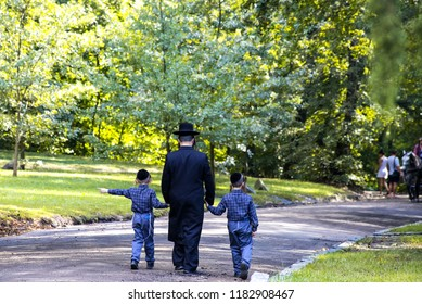 A family of Hasidic Jews, a man with children, walks through the Autumn Park in Uman, Ukraine, Religious Orthodox Jew, Jewish New Year holiday
