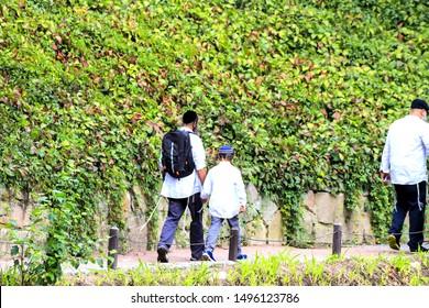 A family of Hasidic Jews, a man with children, walks through the Autumn Park in Uman, Ukraine, Religious Orthodox Jew, Jewish New Year
