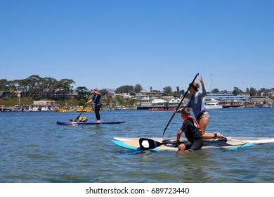 Family have fun on the paddle board on the Pacific Ocean, Morro bay California USA.