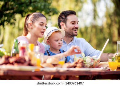 Family having a barbecue in the garden,eating and having fun together. Leisure, holidays, eating, people and food concept.