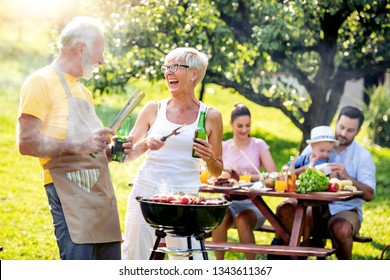 Family having a barbecue in a park.Leisure, food, family and holidays concept.