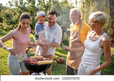 Family having a barbecue party, mother, father son and grandparents standing around the grill.