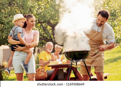 Family having a barbecue party in their garden in summer,enjoying together.