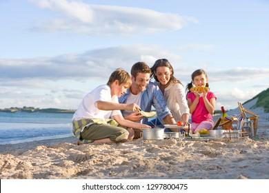 Family having barbecue picnic on sandy beach