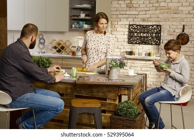 Family having breakfast at home in the kitchen.
