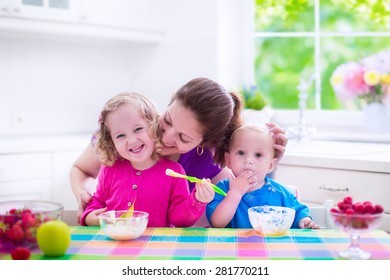Family having breakfast in a white sunny kitchen. Young mother feeding two kids, eating fruit and dairy. Healthy nutrition for children. Parent with toddler kid and baby cooking morning meal.