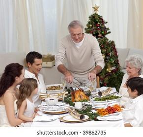Family having Christmas dinner eating turkey at home