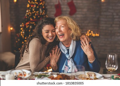Family having Christmas dinner at home, gathered around the table, enjoying their time together; daughter hugging her mother and smiling