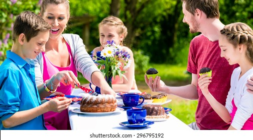 Family having coffee and cake in garden in front of their home at a table outdoors