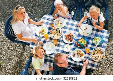 Family having dinner in their garden - barbecue stuff and salad