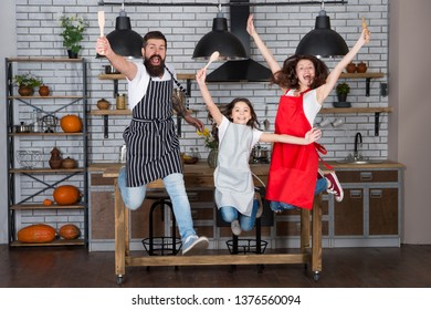 Family having fun cooking together. Teach kid cooking food. Weekend breakfast. Cooking with child might be fun. Having fun in kitchen. Family mom dad and little daughter wear aprons jump in kitchen.