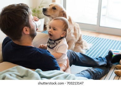 Family having fun with a feeding bottle - Father, baby and dog!