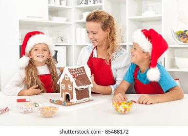 Family having fun in the kitchen while decorating a gingerbread cookie house