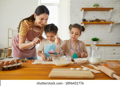 Family having fun making cakes and cookies together. Two little twin sisters cook cookies in the kitchen with their mother, who helps them. Concept of homemade food and little helpers.