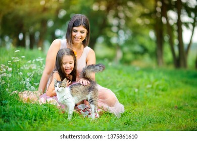 family is having fun. Mom and daughter play in the cat sitting on the grass in the park. people concept. Family enjoy time together