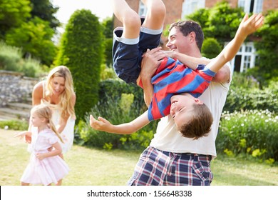 Family Having Fun Playing In Garden