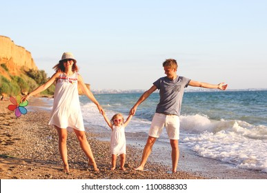 Family having fun playing on the beach at sunset. Family, colour, vacation concept.