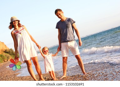Family having fun playing on the beach at sunset. Family, colour, vacation concept. Rainbow flower.