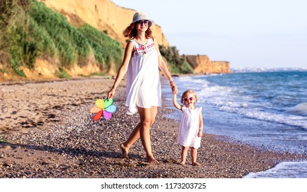 Family having fun playing on the beach at sunset. Mum and girl smiling.Family, colour, vacation concept.