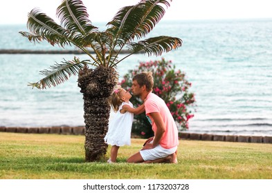 Family having fun playing on the beach at sunset. Dad and girl hugging, kissing. Family, colour, vacation concept.