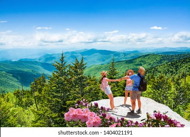Family having fun, relaxing on the top of mountain on vacation hiking trip. People holding hands in circle.  Blue Ridge Mountains, North Carolina, USA.