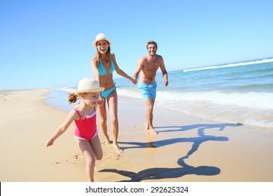Family having fun running on a sandy beach