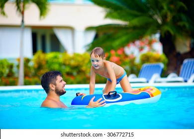 family having fun in swimming pool, summer vacation