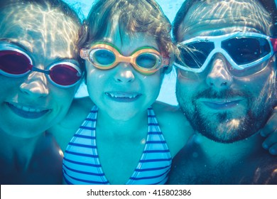 Family having fun in swimming pool. Underwater funny portrait. Summer vacation