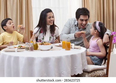 Family having fun while eating pizza together at restaurant