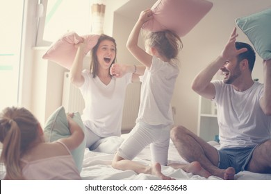 Family having funny pillow fight on bed. Parents spending free time with their daughters.