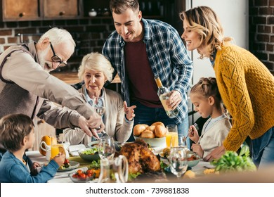 family having holiday dinner and cutting turkey