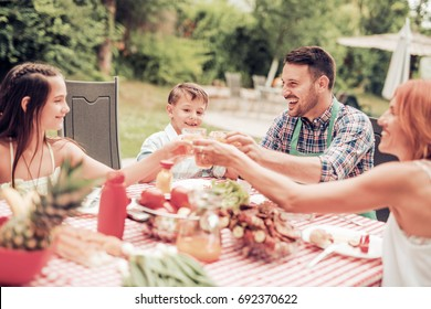 Family having a lunch in their garden in summer.
