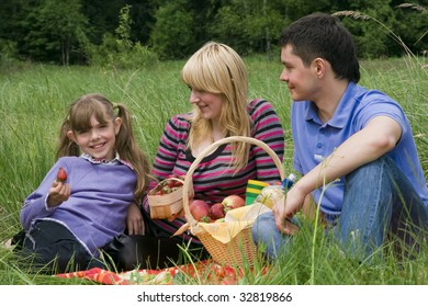 Family having picnic in park. Parents and child on picnic in the forest. Mother, father and daughter relaxing. Girl is holding strawberry.