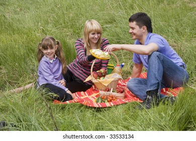 Family having picnic in park. Parents and child on picnic in the forest. Mother, father and daughter relaxing. Wife is giving husband sandwich.