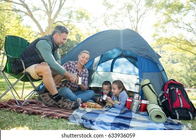 Family having snacks and coffee outside the tent at campsite