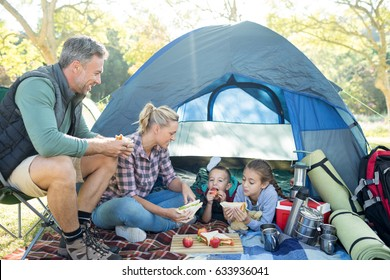 Family having snacks outside the tent at campsite
