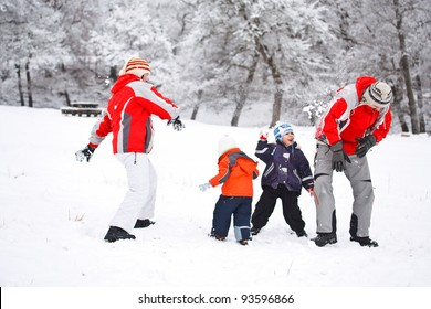 Family having snowball fight in snow in winter background
