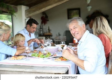 Family having summmer lunch in country house