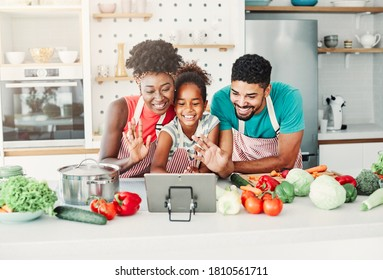 Family  having a video call over tablet while preparing meal and having fun in the kitchen at home